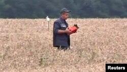 En la imagen se observa un individuo con lo que se estima sería una caja negra del avión malasio que cayó en Ucrania.