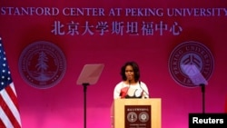 U.S. first lady Michelle Obama gives a speech next to American (L) and Chinese national flags at the Peking University in Beijing, March 22, 2014.