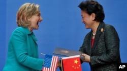 2012年5月21日美国国务卿克林顿(左)与中国国务委员刘延东在签署协议后握手(资料照片)