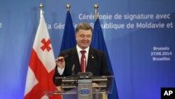 Tổng thống Ukraine Petro Poroshenko cầm cây bút sau khi ký hiệp định tại hội nghị thượng đỉnh EU ở Brussels, 27/6/14