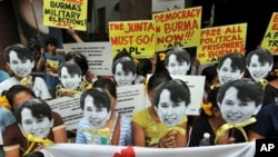 Activists from the Free Burma Coalition holding masks depicting Burmese democracy icon Aung San Suu Kyi hold a rally in front of the Burmese embassy in Manila, 17 Nov 2010