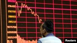 Seorang investor mengamati monitor yang menyajikan informasi indeks bursa saham Shanghai di Beijing (26/8).