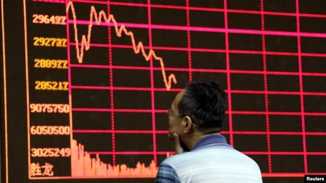 Nhà đầu tư nhìn vào bảng hiển thị thông tin chứng khoán điện tử của thị trường chứng khoán Thượng Hải tại Trung tâm môi giới chứng khoán ở Bắc Kinh.