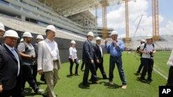 Jerome Valcke, secretario general de la FIFA (centro) y otras personalidades visitan el estadio Arena de Sao Paulo, durante una gira de inspección de los escenarios del Mundial 2014.