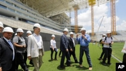 Sekjen FIFA Jerome Valcke (tengah) dan Menteri Olahraga Brazil Aldo Rebelo (mengenakan jaket tipis), menginspeksi stadion Arena de Sao Paulo, Brazil, 20 Januari 2014 (Foto: dok).