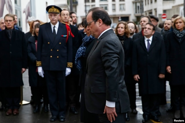 French President Francois Hollande (C) and Paris Mayor Anne Hidalgo attend a ceremony to unveil a commemorative plaque to pay tribute to the victims of the last year's January attacks outside the former offices of French weekly satirical newspaper Charlie Hebdo, Jan. 5, 2016.