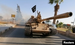 FILE - Militant Islamist fighters on a tank take part in a military parade along the streets of northern Raqqa province, June 30, 2014.