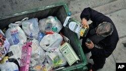Čovjek prazni ostatke odbačene limenke maslinova ulja iz smeća u Grčkoj