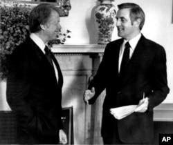 FILE - Then-Vice President Mondale, right, briefs President Jimmu Carter on his trip to Europe in the Oval Office In Washington, May 24, 1977.