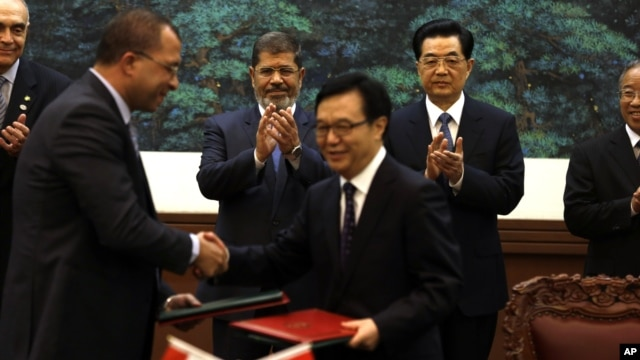 Egyptian President Mohammed Morsi, center left, and Chinese President Hu Jintao, center right, applaud as officials exchange documents during a signing ceremony in Beijing, China, August 28, 2012.