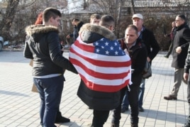 A male protester drapes himself with an American flag, Jan. 9, 2016. Many Kosovars still hold the United States in high regard after it led NATO airstrikes in 1999, which eventually helped the country gain independence from Serbia. (P.W. Wellman/VOA)