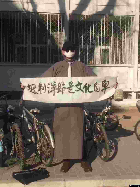 """互联网上流传的照片显示有个捂得严严实实的人打出标语:""""抵制洋节是文化自卑""""。据说此举发生在北京大学。美联社报道,今年至少有四个中国城市和一个县已经下令限制圣诞节庆祝活动。 另一个城市的教堂已经得到警告要让未成年人远离圣诞节,全国至少有十所学校在校园内限制圣诞节活动。"""