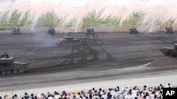Tank milik Pasukan Darat Bela Diri Jepang mengepulkan asap dalam latihan menembak tahunan di wilayah Higashi Fuji, Gotemba, barat daya Tokyo, Selasa, 20 Agustus, 2013. (AP Photo / Koji Sasahara)