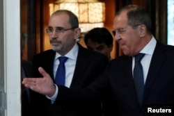 FILE - Russian Foreign Minister Sergey Lavrov and Jordanian Foreign Minister Ayman Safadi enter a hall during a meeting in Moscow, Russia, July 4, 2018.