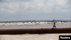 FILE - A man walks on a pipeline on the outskirt of Nigeria's commercial capital Lagos, June 25, 2016.