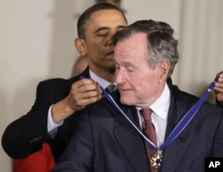 President Barack Obama awards former President George H.W. Bush the 2010 Medal of Freedom during a ceremony in the East Room of the White House in Washington, Tuesday, Feb. 15, 2011.
