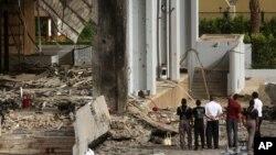 Civiles observan los escombros del hotel Babil, en Bagdad, donde un coche bomba estalló este viernes.