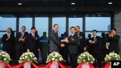 A 2006 photo shows Intel CEO Paul Otellini (C-L) presenting a gift to Li Chuncheng, who was secretary of Chengdu Municipal Committee of the Communist Party, during the completion ceremony of the second project of Intel Products Chengdu Ltd. in Chengdu, Sichuan province.