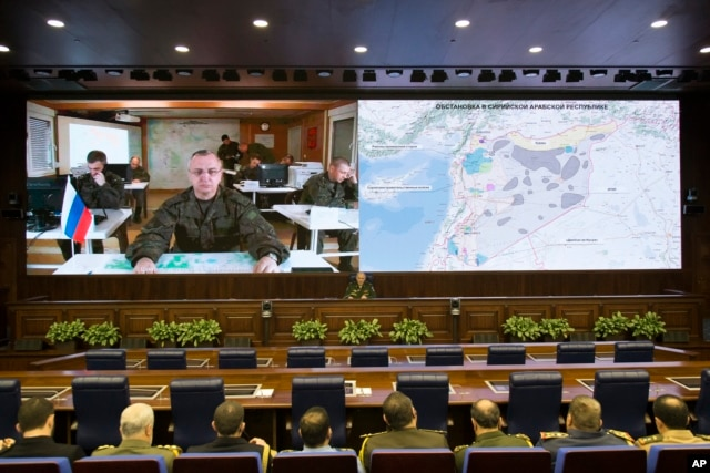 Lt.-Gen. Sergei Rudskoi of the Russian Military General Staff, background center, speaks to the media in Moscow, Feb. 27, 2016. A top military official said Russia has halted airstrikes in areas where armed groups said they would abide by a cease-fire.