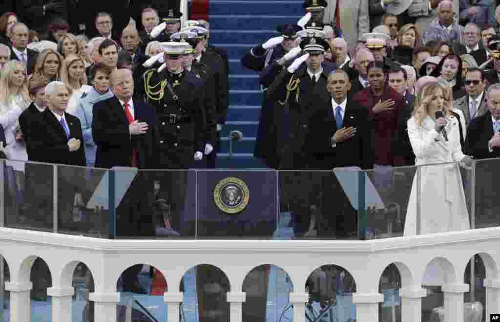 美国总统川普和副总统彭斯倾听16岁的美国女歌手杰基·伊万科(Jackie Evancho)在国会大厦前面举行的就职大典上演唱美国国歌(2017年1月20日)