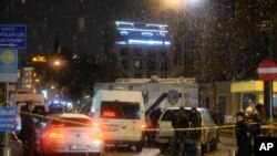 Turkish security gather outside a police station where one police officer was killed and another injured after a suicide bomber blew herself up in Istanbul.