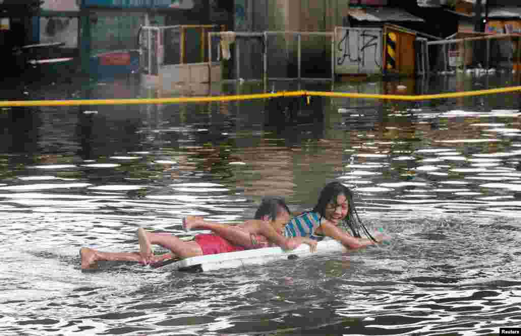 Children use a makeshift raft as they play along a partially flooded street caused by monsoon rains and Tropical Storm Son-Tinh in Quezon city, Metro Manila, in Philippines, July 17, 2018.