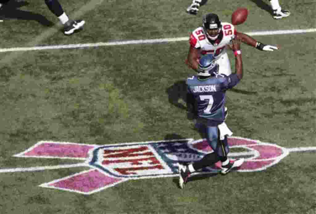 El mariscal de campo de los Seahawks de Seattle, Tarvaris Jackson, corre a lo largo del lazo rosado del NFL que apoya la lucha contra el cáncer de mama.