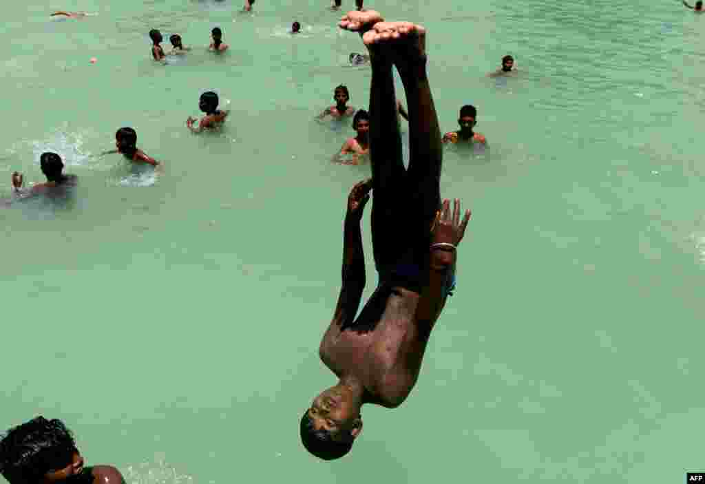 Indian youths swim during a hot day in Chennai.