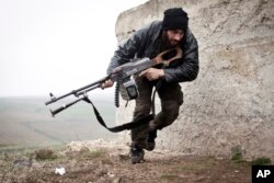 FILE - A Free Syrian Army fighter takes cover during fighting with the Syrian Army in Azaz, Syria.