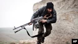 Un combatiente del Ejército Siria Libre busca cubrirse del fuego enemigo en Azaz, Siria.