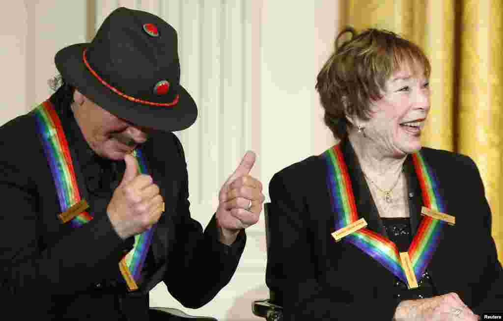 Carlos Santana and fellow 2013 Kennedy Center Honors recipient Shirley MacLaine react to remarks by U.S. President Barack Obama during a reception at the White House, Dec. 8, 2013.