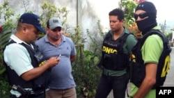 Polisi Honduras mengawal Plutarco Antonio Ruiz (kedua dari kiri), pacar Sofia, kakak ratu kecantikan Honduras, Maria Jose Alvarado, di Santa Barbara (18/11).