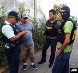 National Police agents escort Plutarco Antonio Ruiz (2nd-L), the boyfriend of Miss Honduras Maria Jose Alvarado's sister, in Santa Barbara, 200 kms north of Tegucigalpa, Nov. 18, 2014.