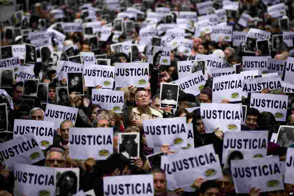 "People hold up signs that read in Spanish ""Justice"" and pictures of the victims of the bombing of the AMIA Jewish community center on the 19th anniversary of the terrorist attack in Buenos Aires, Argentina. The bombing of the Argentine-Israeli Mutual Association killed 85 people in 1994 and remains unsolved."