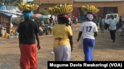 Faridah Hussein (No. 17 T-shirt on right) carries bananas into a market in Juba. The 33-year-old mother of three doesn't put the 15-20 South Sudanese pounds she makes a day by selling the bananas in a bank because she thinks she earns too little to open an account.
