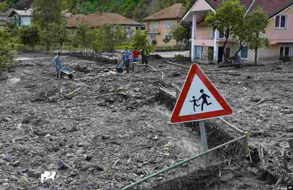 Residents walk on streets covered with mud and rubble after a landslide at the village of Topcic Polje, near Zenica, Bosnia-Herzegovina, May 20, 2014.