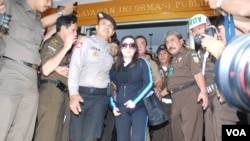 Buron terpidana kasus korupsi Kredit Likuiditas Bank Indonesia, Sherny Kojongian Saroha (tengah) dikawal oleh polisi saat tiba di Jakarta dari San Fransisco, AS, Rabu (13/6). Tertangkapnya Sherny Kojongian menimbulkan pertanyaan, apakah pemerintah akan se