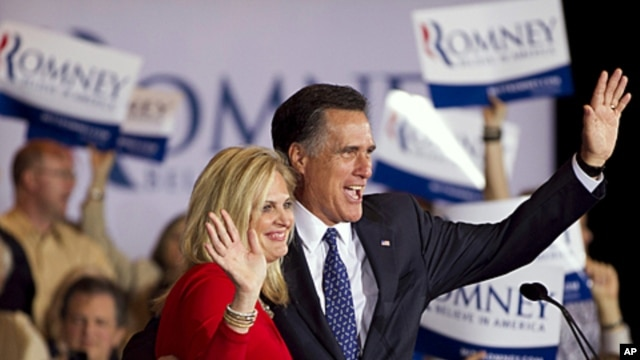 Republican presidential candidate Mitt Romney, right, and his wife Ann wave to a crowd in Schaumburg, Illinois, after Romney won the Illinois Republican presidential primary, March 20, 2012.