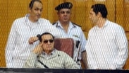 FILE -  former Egyptian president Hosni Mubarak, seated, and his two sons Gamal Mubarak (L) and Alaa Mubarak (R) are seen attending a hearing in a Cairo courtroom Sept. 14, 2013.