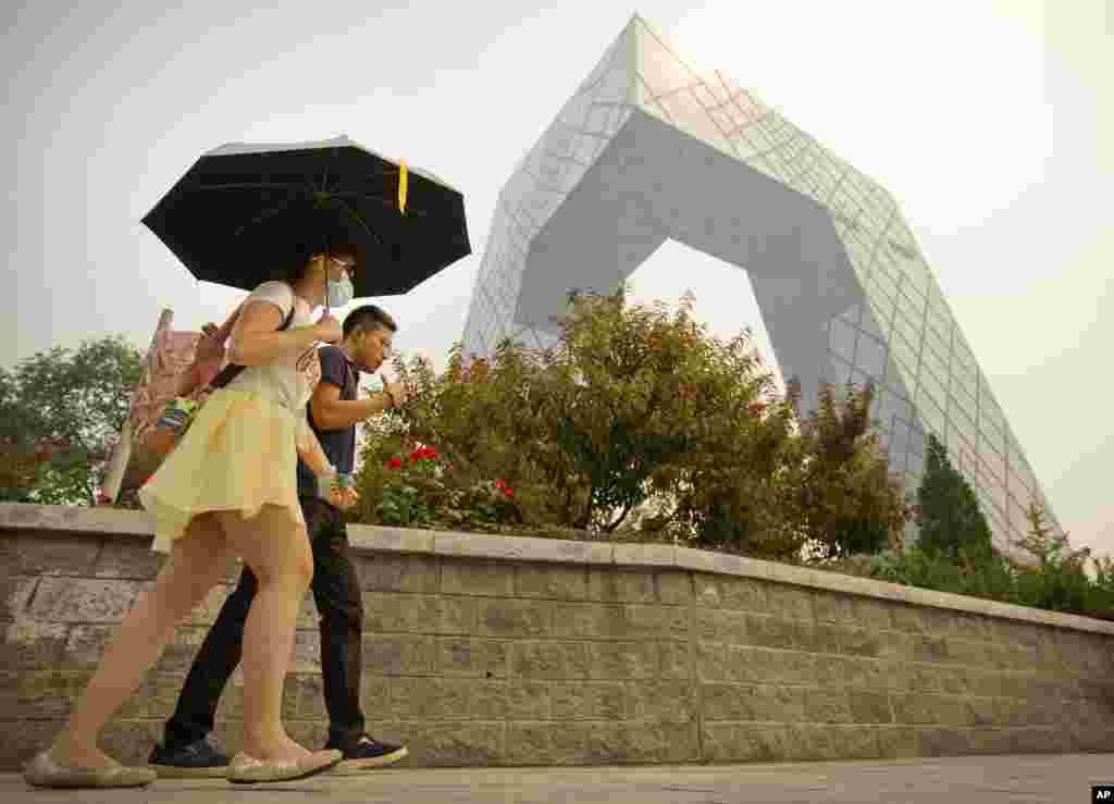 """有人打雨伞戴口罩从北京中央电视台大楼旁走过(2015年)。在外界猜疑声中,央视在2017年播出报道《海航24年前行的力量》。海航网站介绍这个节目说,它讲述了海航从""""那个春天,是万物生长的季节,几个南下的年轻人,在中国最年轻的省份,开始了他们的创业梦"""",到用胆识、智慧和分享的理念开启国际化发展,成长为全球大型企业集团的发展历程。"""