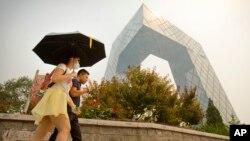 Seorang perempuan mengenakan masker di suatu hari yang penuh asap dan kabut di China