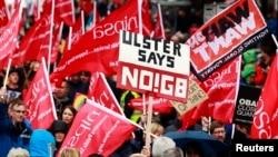 ພວກປະທ້ວງພາກັນຖືປ້າຍ ແລະໂບກທຸງ ໃນລະຫວ່າງການເດີນຂະບວນຢູ່ກາງນະຄອນ Belfast ໃນວັນທີ 15 ມິຖຸນາ, 2013, ເພື່ອຕໍ່ຕ້ານກຸ່ມ G8 ກ່ອນກອງປະຊຸມ ສຸດຍອດຂອງກຸ່ມດັ່ງກ່າວ ຈະຈັດຂຶ້ນໃນບ່ອນຕາກອາກາດ Lough Erne, ໄອແລັນເໜືອ ໃນວັນທີ 17 ແລະ 18 ມິຖຸນາ 2013 ຈະມາເຖິງນີ້.