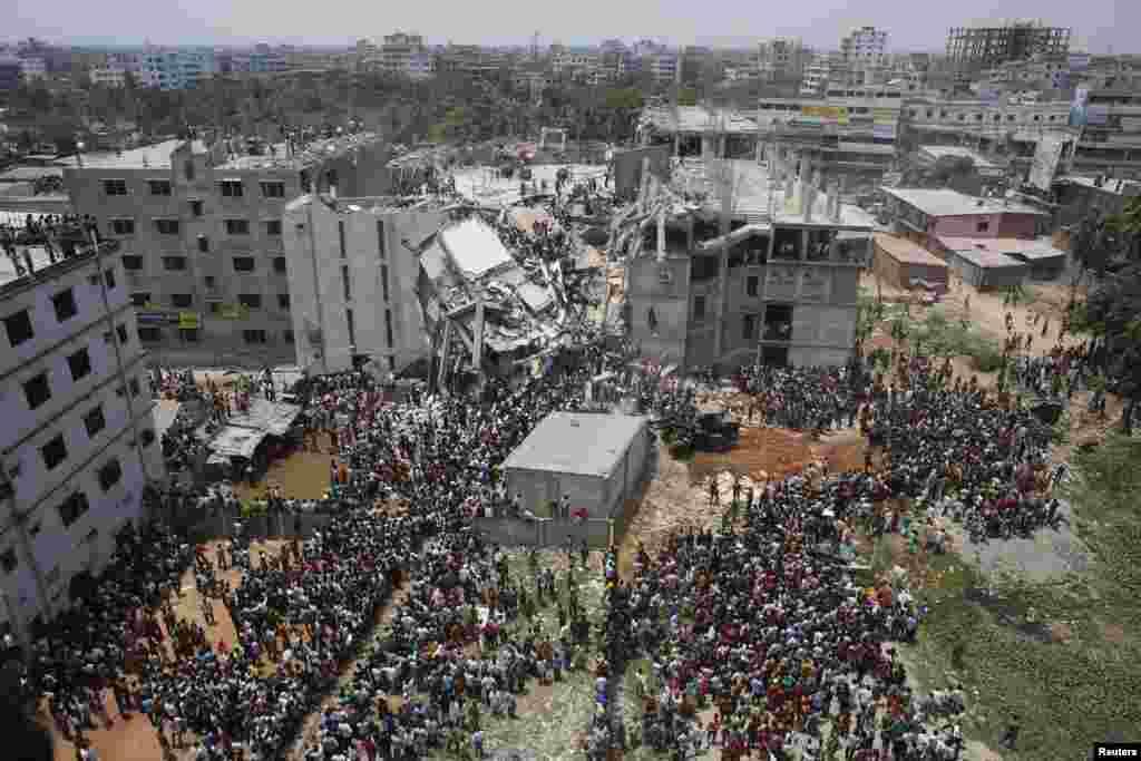 Đám đông tụ tập tại tòa nhà thương mại 8 tầng ở Savar bị sập trong lúc nhân viên cứu hộ giải cứu công nhân may mặc bị kẹt dưới đống đổ nát, ngày 24/4/2013.