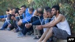 Beberapa pria dengan tang an terikat duduk setelah ditangkap oleo polisi perbatasan Israel dalam sebuah razia untuk menghalau imigran yang masuk secara ilegal di wilayah Petah Tikva (30/11).