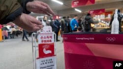 A man sanitizes his hands at the entrance to the media cafeteria, Feb. 7, 2018 in Gangneung, South Korea. There are concerns over the possible spreading of the norovirus, a contagious virus that causes stomach pain, nausea and diarrhea.