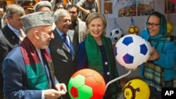 Afghan President Hamid Karzai and U.S. Secretary of State Hillary Rodham Clinton tour a crafts bazaar in Kabul as they attend an international conference on Afghanistan.