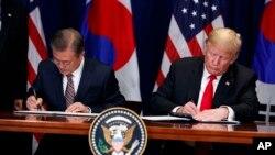 Perezida Donald Trump, iburyo, na Perezida wa Koreya y'epfo Moon Jae-In batera imikono ku masezerano y'Ubudandaji, New York Palace hotel, itariki 24/09/2018.
