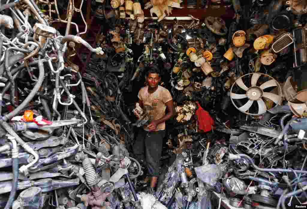 A worker carries a piece from a used car inside a shop at a second-hand automobile parts market in Mumbai, India.