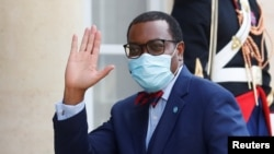 FILE - President of the African Development Bank, M. Akinwumi Adesina waves as he arrives for a dinner with French President Emmanuel Macron and leaders of African states and international organisations on the eve of a summit on aid for Africa, at Elysee