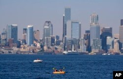 Kayakers and boaters ply the waters of Elliott Bay with the Seattle skyline behind during a heat wave hitting the Pacific Northwest, Sunday, June 27, 2021. (AP Photo/John Froschauer)